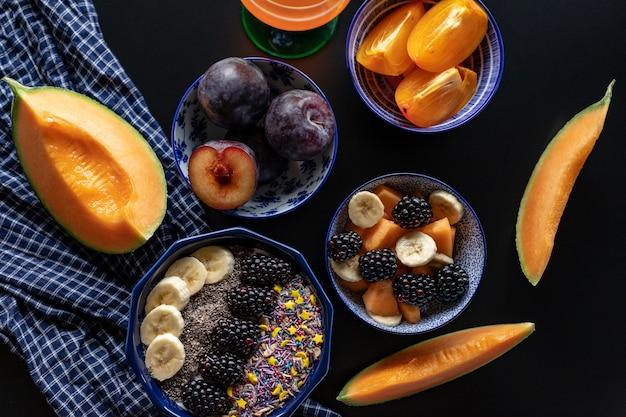 Miska śniadaniowa z płatkami owsianymi, jogurtem, jeżynami, persimmon, melonem i nasionami chia, widok z góry