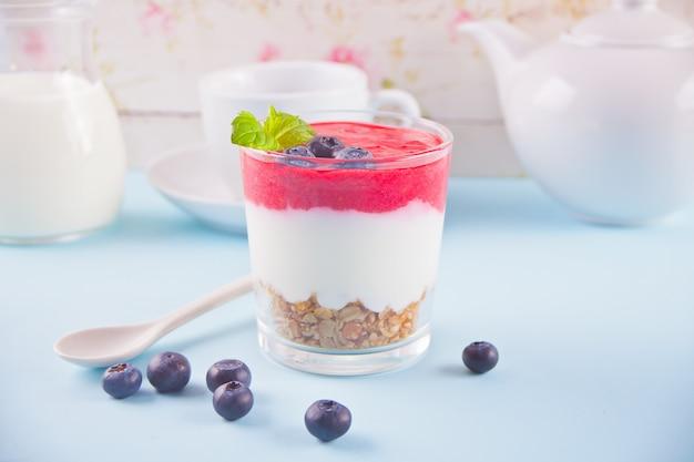 Miska śniadaniowego zdrowego musli z jagodami, truskawkami i jogurtem.