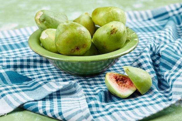 Miska soczystych zielonych fig i plasterek fig na niebieskim obrusie.