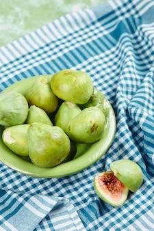 Miska soczystych zielonych fig i plasterków fig na niebieskim obrusie.