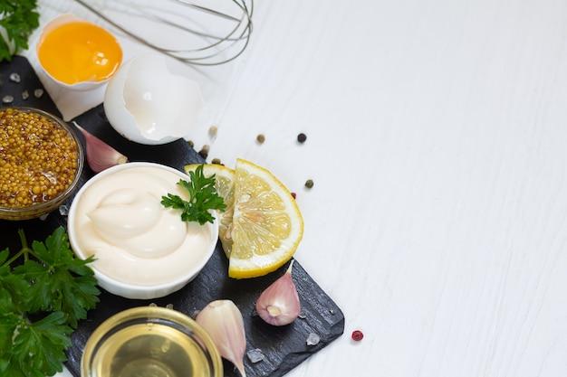 Miska sosu majonezowego obok składników do robienia domowych sosów
