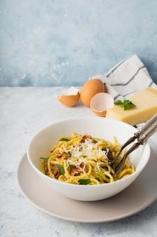 Miska spaghetti pod wysokim kątem z parmezanem i jajkami