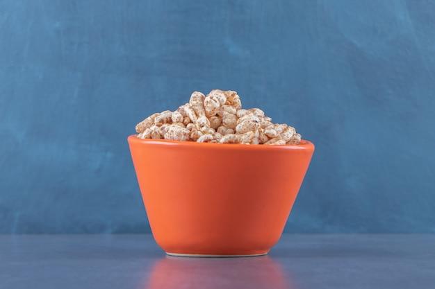 Miska suchych płatków kukurydzianych na niebieskim stole.