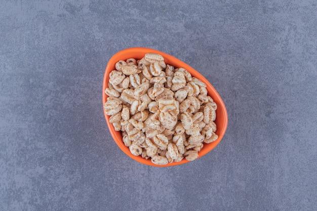 Miska suchych płatków kukurydzianych, na niebieskim tle. zdjęcie wysokiej jakości