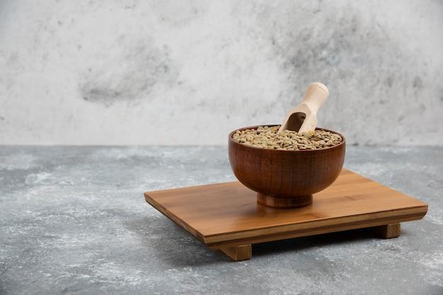 Miska surowego groszku łuskanego ułożona na drewnianej desce.