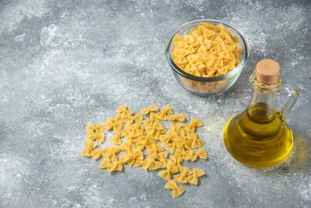 Miska surowego makaronu farfalle z butelką oliwy z oliwek na tle marmuru.