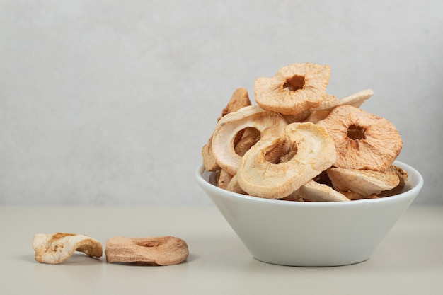 Miska suszonych krążków jabłek na białej powierzchni