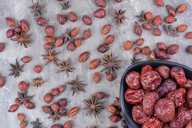 Miska suszonych owoców dzikiej róży na kamiennym stole.