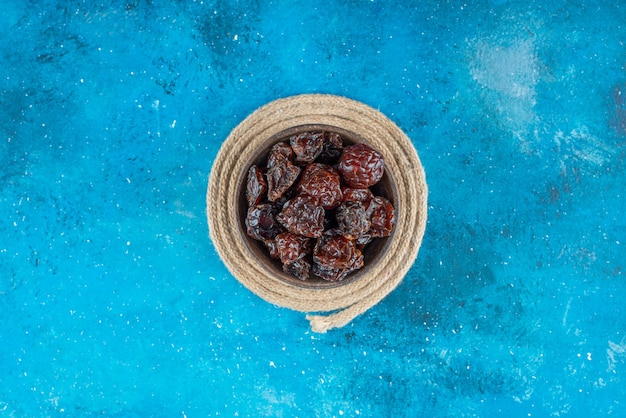 Miska suszonych śliwek na podstawce, na niebieskim stole.