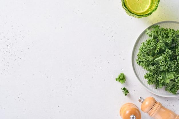 Miska świeżego zielonego posiekanego jarmużu na jasnoszarym tle kamienia, widok z góry. składnik do przygotowania zdrowej sałatki.
