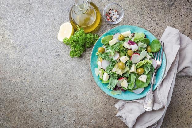 Miska świeżej sałatki zdrowej z warzywami i zielenią na szaro