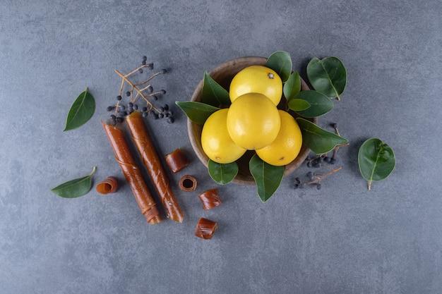 Miska świeżych cytryn i zielonych liści na szarym tle.