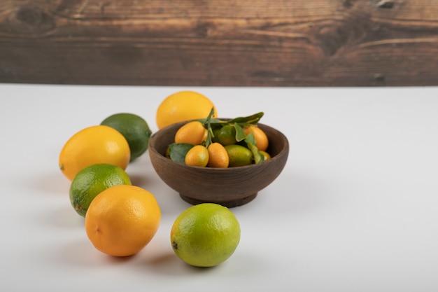 Miska świeżych kumkwatów, limonek i cytryn na białym tle.
