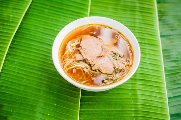 Miska tradycyjnej wietnamskiej zupy wołowej pho bo na tle liści bananów.