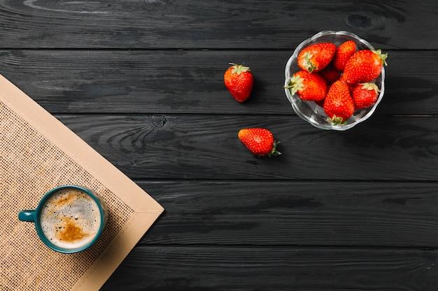 Miska truskawek i filiżanki kawy na podkładce jutowej na czarnej powierzchni teksturowanej