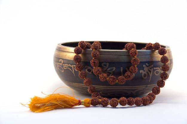 Miska tybetańskiego śpiewu z wygrawerowanym mantrą i widokiem z boku rudraksa na białym tle