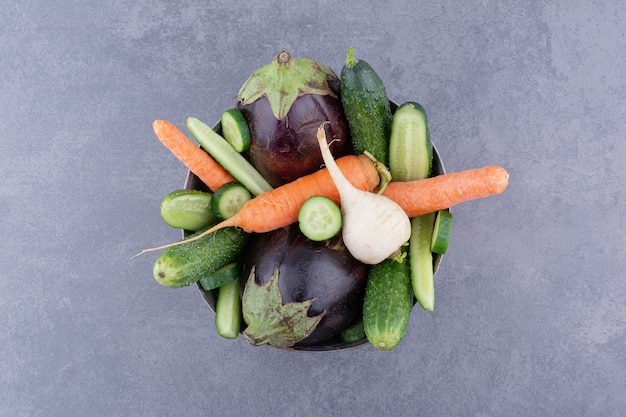 Miska warzyw na białym tle na tle betonu.