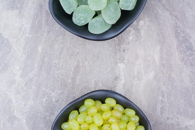 Miska winogron i cukierki marmolady na tle kamienia.
