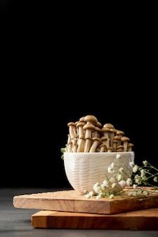Miska wypełniona grzybami na drewnianej podstawie