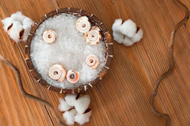 Miska z białą grubą solą do procedur wodnych na naturalnym drewnie.