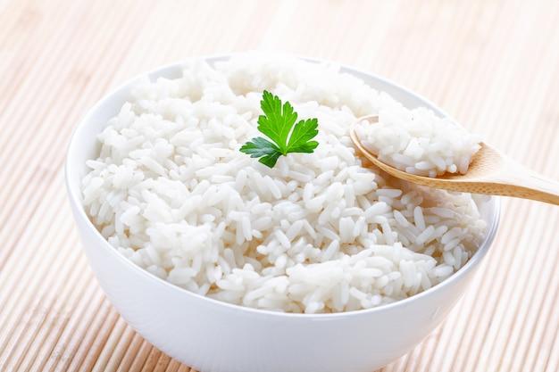 Miska z białym gotowanym ryżem z zieloną świeżą pietruszką na pyszny zdrowy lunch. produkty zbożowe i potrawy.