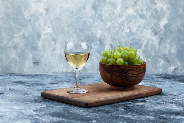 Miska z bliska białych winogron, kieliszek whisky na desce do krojenia na ciemnym i jasnoniebieskim tle marmuru. poziomy