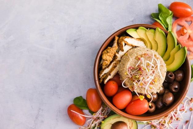 Miska z burrito z ryżem; kiełkować; pomidor; awokado i oliwka na betonowym tle