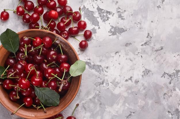 Miska z czerwonymi wiśniami na szarym tle.