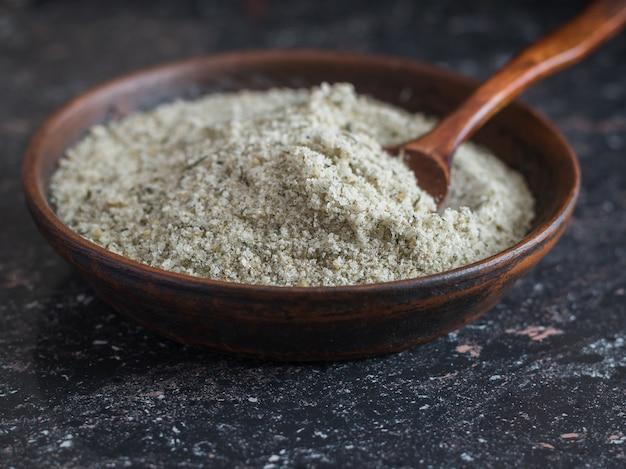Miska z gliny z łyżką wypełnioną solą z ziołami na kamiennym stole.