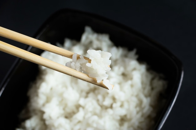 Miska z gotowanym ryżem na czarnym tle. azjatyckie jedzenie i pałeczki bambusowe.