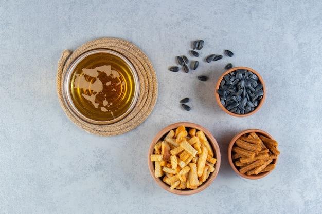 Miska z grzankami i nasionami obok piwa w szklance, na marmurowej powierzchni.