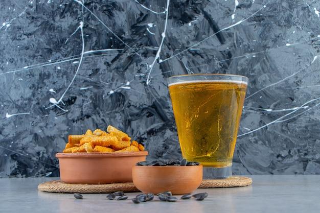 Miska z grzankami i nasionami obok piwa w szklance, na marmurowym tle.