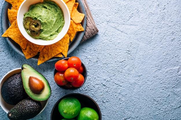 Miska z guacamole meksykańskim na vintage drewnianym stole, w otoczeniu pomidorów, papryki jalapeños, limonki i awokado. copyspace
