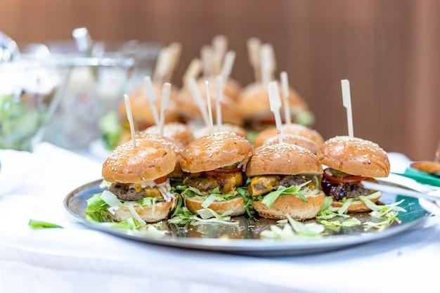 Miska z hamburgerami na stole cateringowym.