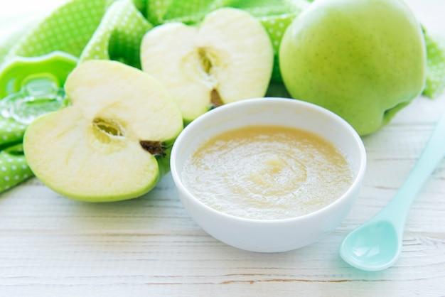Miska z jedzeniem dla dzieci i jabłkami na stole