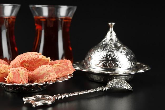 Miska z kawałkami tureckiej rozkoszy i czarnej herbaty