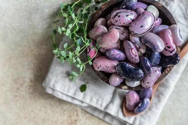 Miska z kolorowymi roślinami strączkowymi i tymiankiem, betonowe tło. wegański produkt wysokobiałkowy. widok z góry.