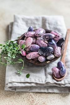 Miska z kolorowymi roślinami strączkowymi i tymiankiem, betonowe tło. wegański produkt wysokobiałkowy.