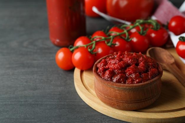 Miska z koncentratem pomidorowym na ciemnym drewnianym stole ze składnikami