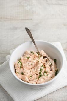 Miska z łososia w pasztecie z miękkim serem i ziołami, tekstylna serwetka na drewnianym stole