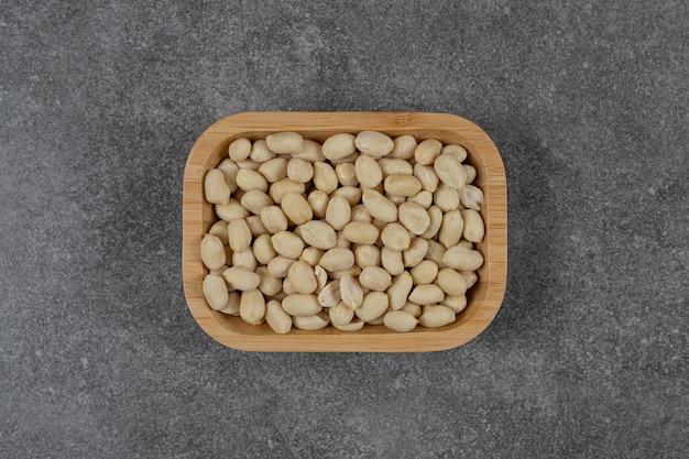 Miska z łupin mniej orzeszków ziemnych na marmurowej powierzchni