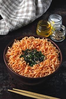 Miska z makaronem chińskim. miska makaronu pomidorowego. kolorowe zdrowe jedzenie w stylu płaskiej świeckich
