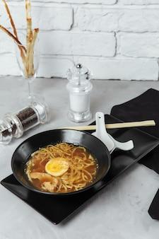 Miska z makaronem ramen z kurczakiem i jajkiem, japońskie jedzenie. chińskie jedzenie. kuchnia tajska. azjatyckie fast foody.