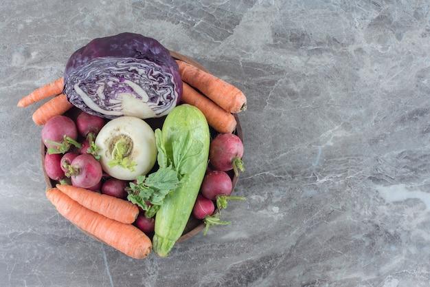 Miska z marchewką, dynią, rzepą, czerwoną kapustą i zieleniną rzepy na marmurze.
