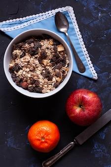 Miska z musli, jabłkiem i mandarynką za pomocą łyżki i noża oglądanego z góry
