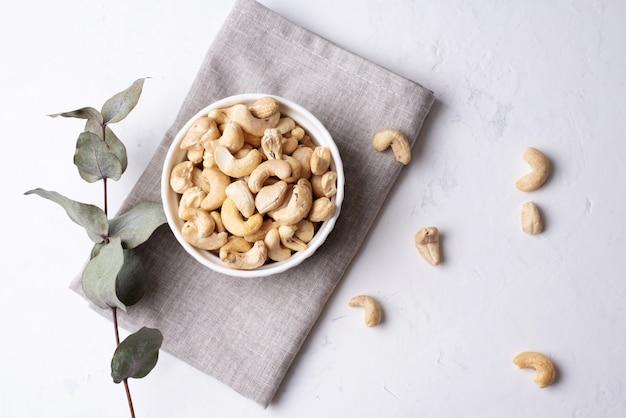 Miska z orzechami nerkowca na białym tle z tekstyliami, wegetariańska zdrowa żywność, z bliska.