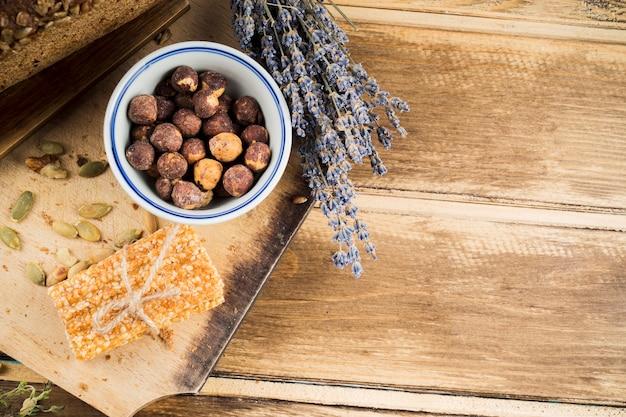 Miska z orzechów laskowych; lawenda i sezamowy pasek związany sznurkiem na desce do krojenia