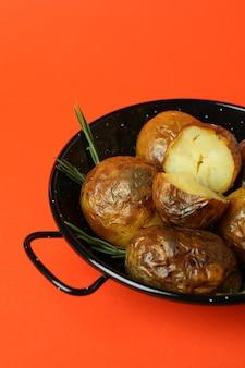 Miska z pieczonym ziemniakiem na pomarańczowym tle.