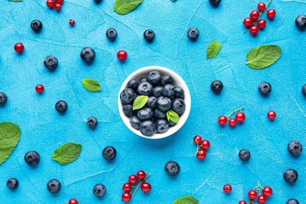 Miska z płaskim układem i porozrzucane jagody z liśćmi