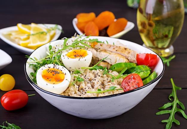 Miska z płatkami owsianymi, filetem z kurczaka, pomidorem, sałatą, mikrogreenami i gotowanym jajkiem